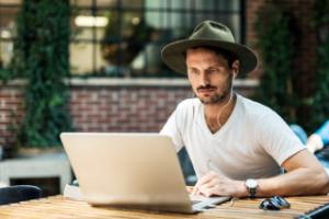 Mann med hatt sitter foran PC på café