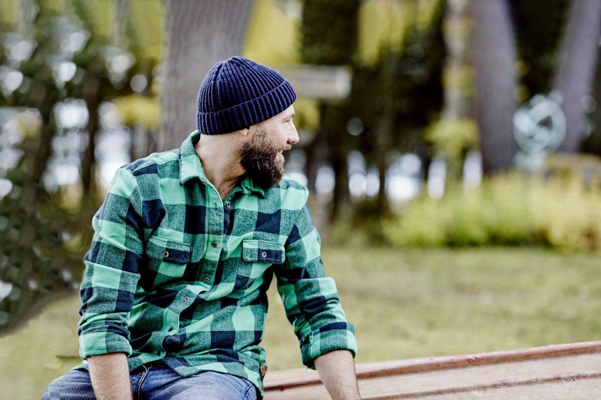 Mann sitter ute iført grønnrutete skjorte og blå lue