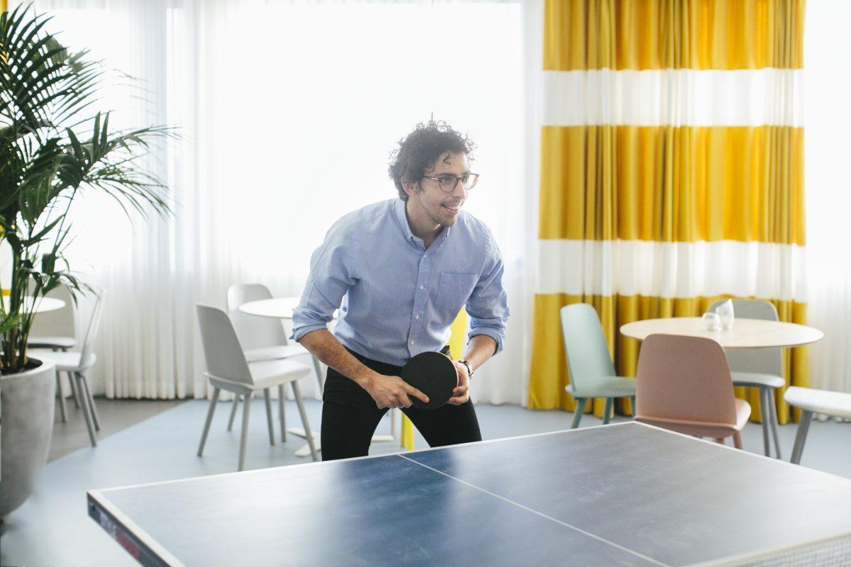Mann i jobbantrekk spiller bordtennins