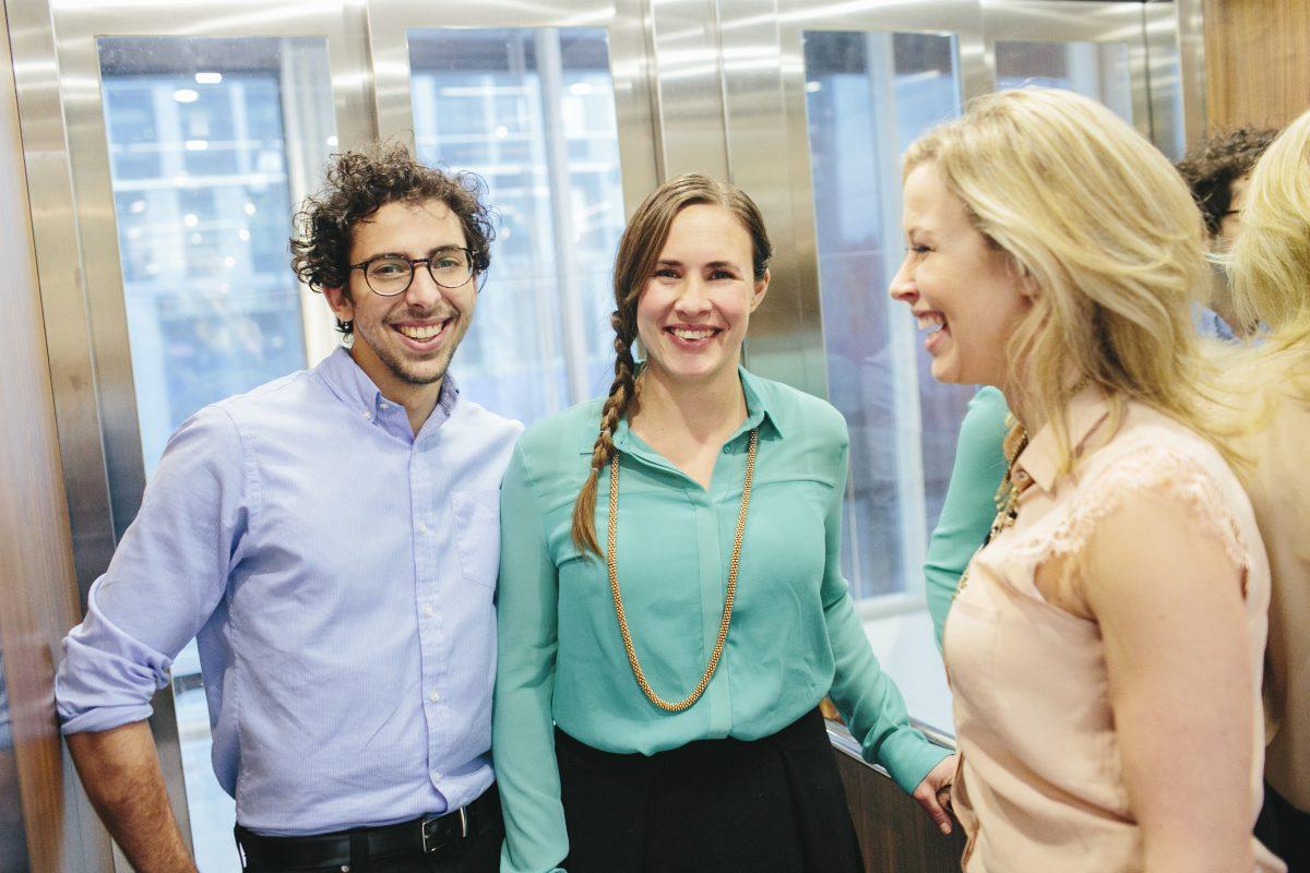 En mann og to kvinnelige kolleger smiler i heisen på jobb