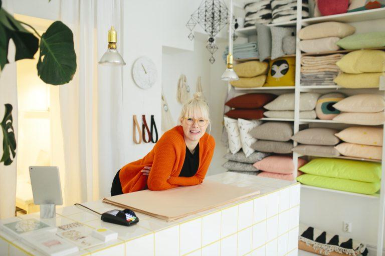 Dame står bak disken i tekstilbutikk