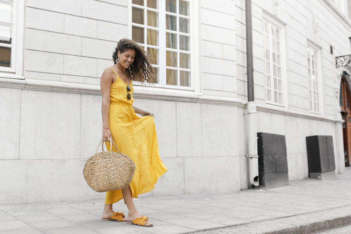 Kvinne i gul sommerkjole på gaten