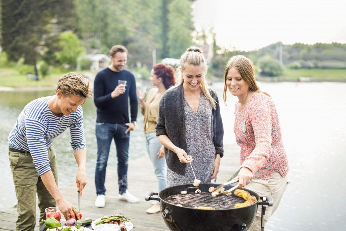 Gruppe yngre mennesker griller, spiser, drikker og hygger seg på en liten brygge ved vannkanten