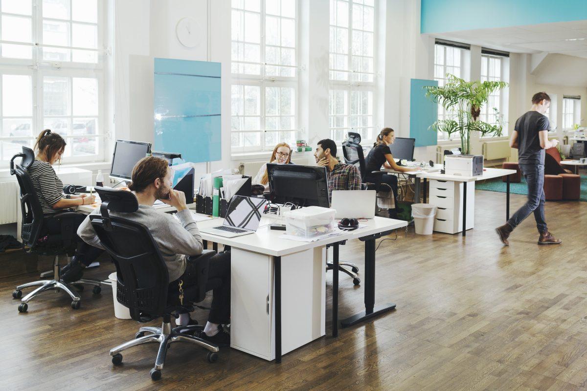 Arbeidsplass med PC-er og mennesker som snakker sammen