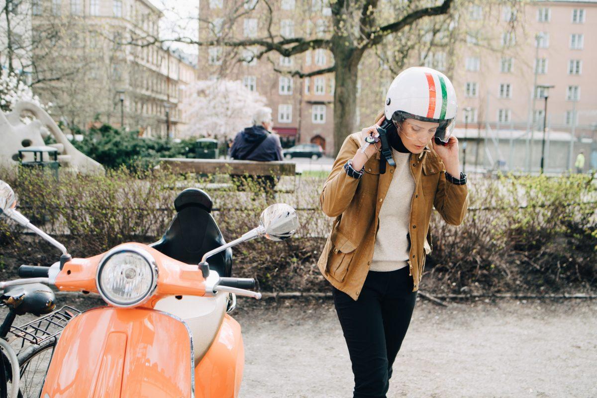 Ung kvinne med en moped ved en park