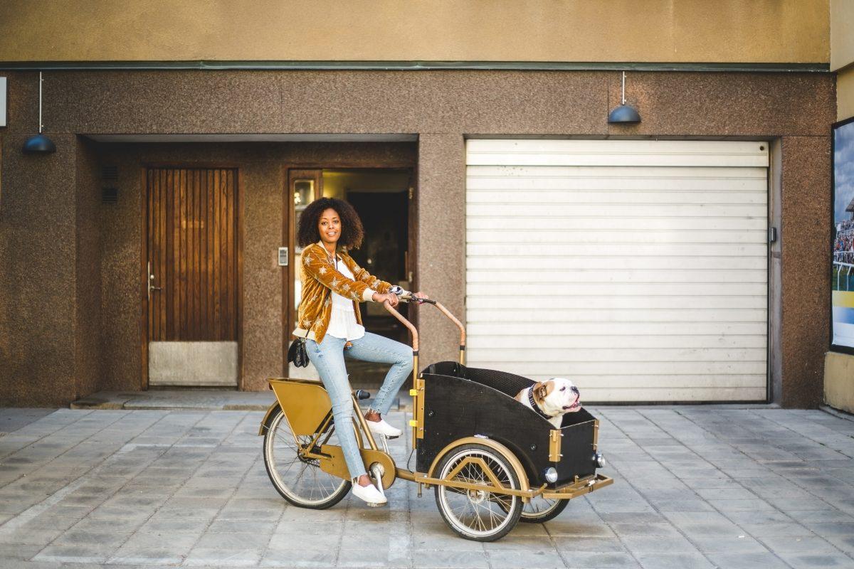 Ung kvinne på sykkel med hund