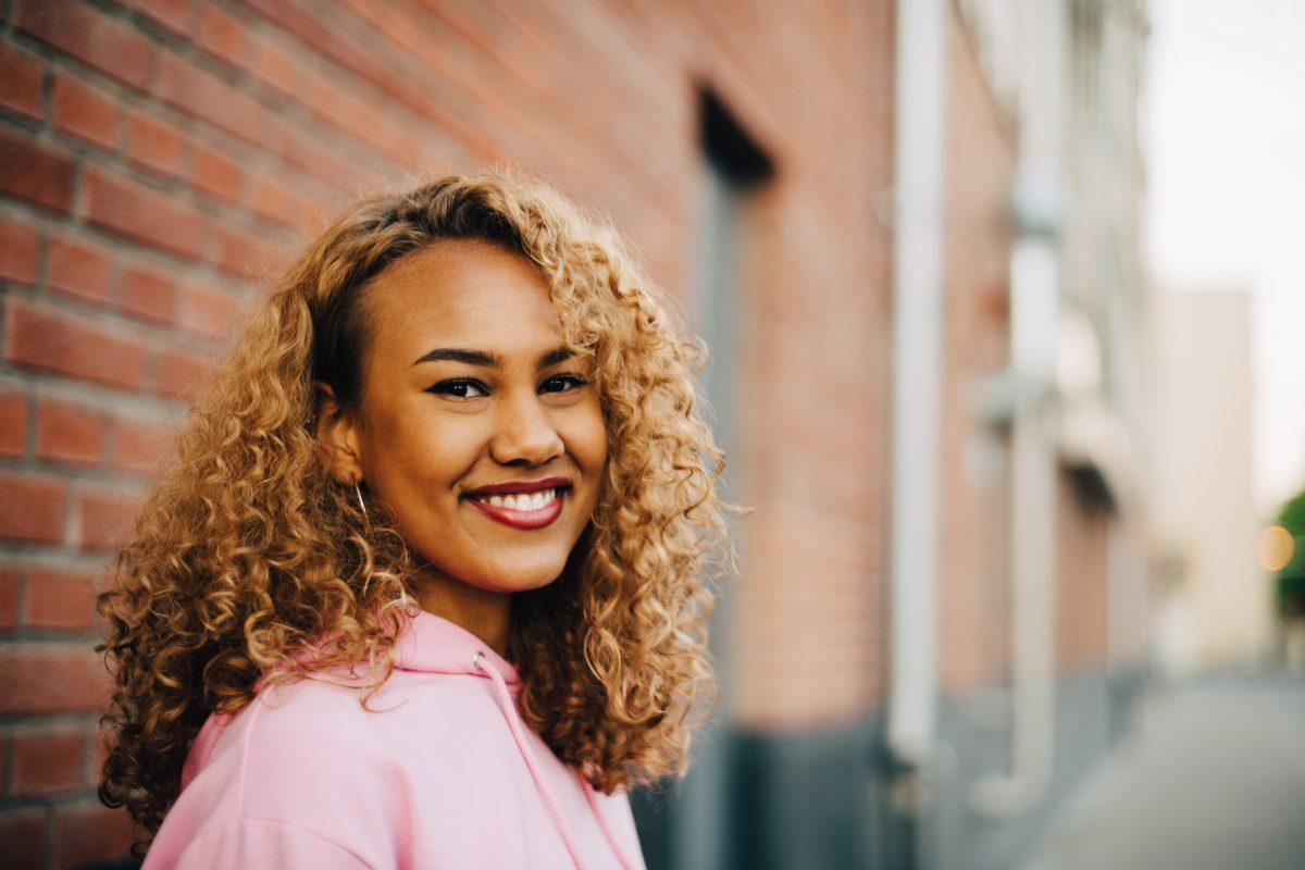 Ung kvinne smiler til kamera foran murbygning