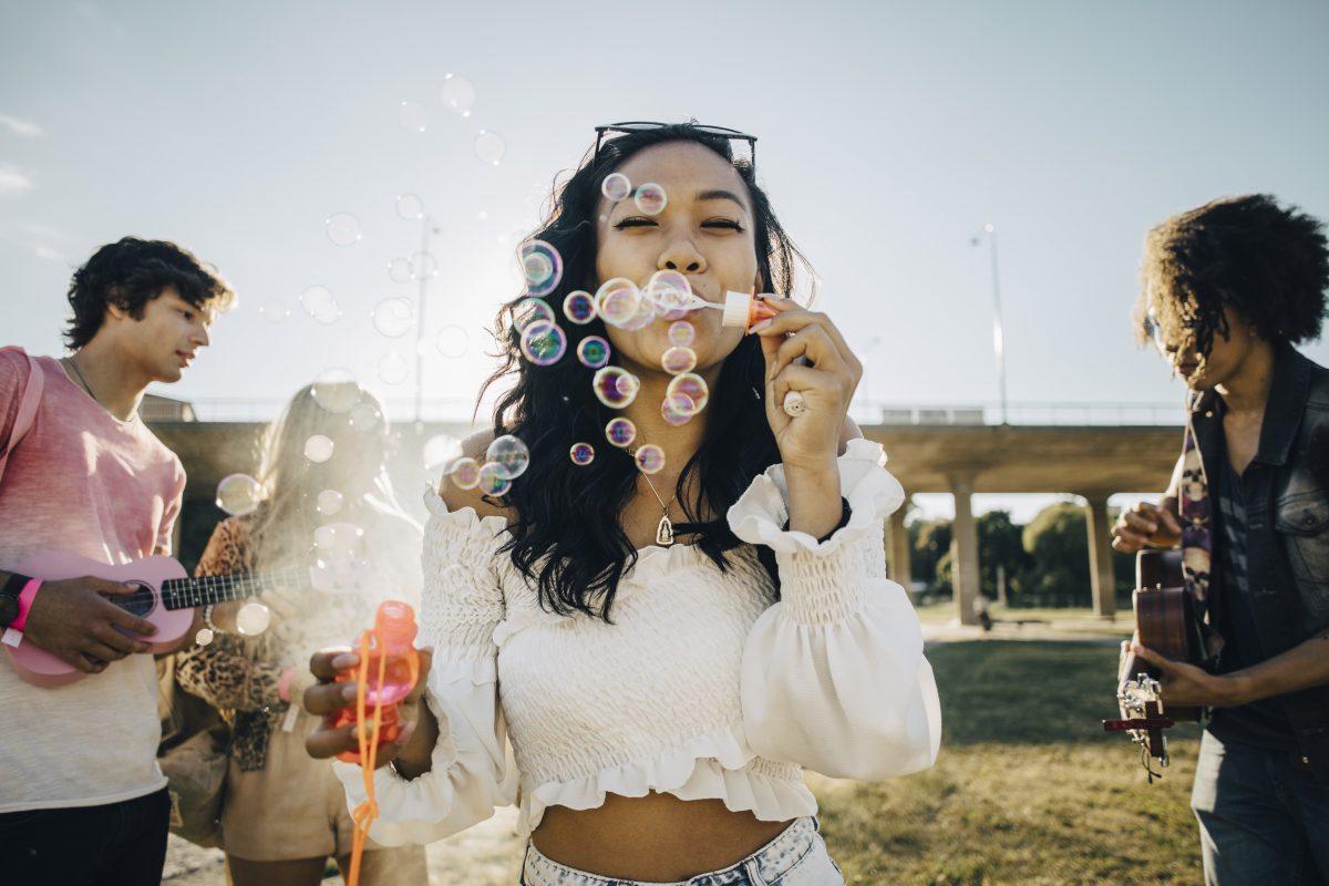 Kvinne blåser såpebobler med venner bak som spiller gitar ute