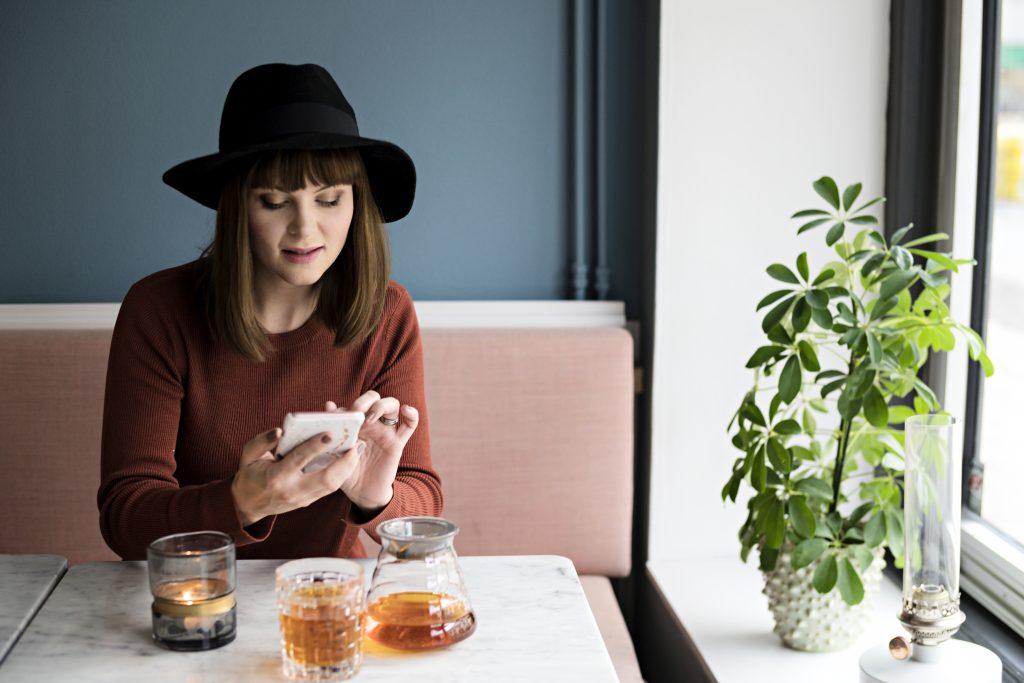 Dame som sitter på kafe med mobiltelefon