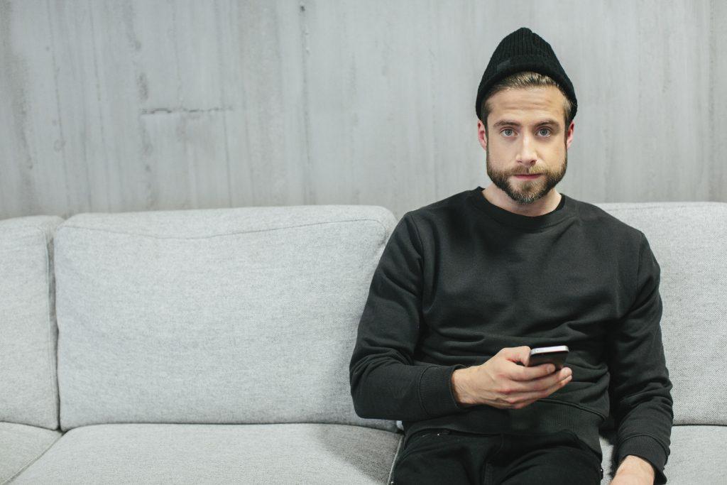Mann som sitter i sofa
