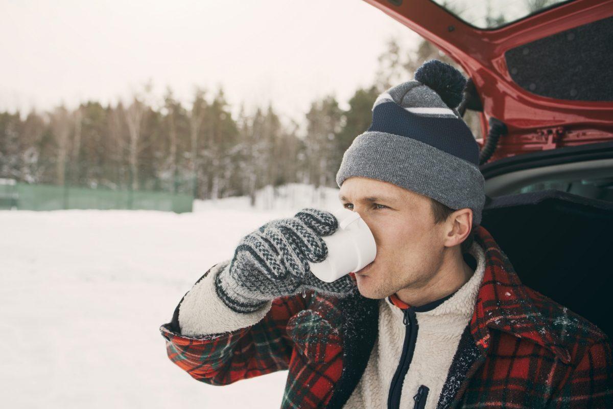 Mann drikker kaffe fra bilen på vinteren