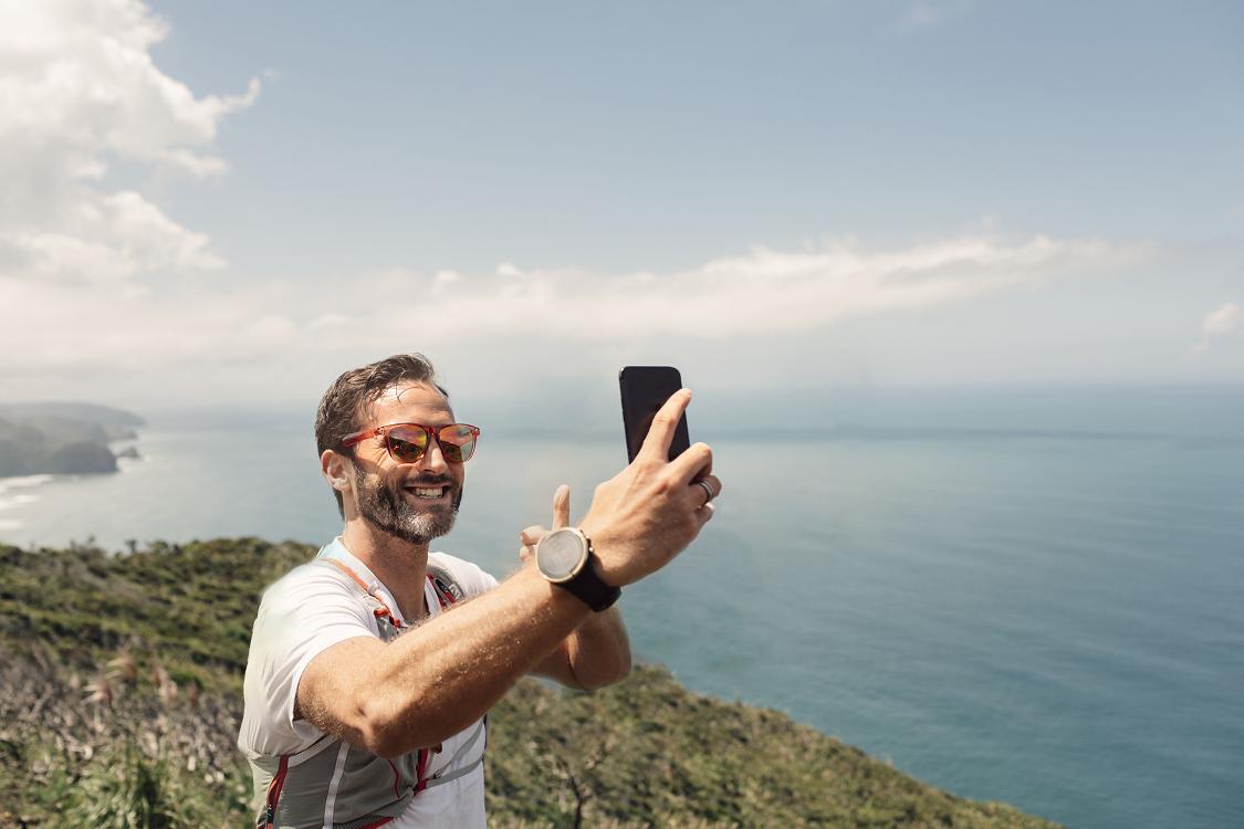Mann med solbriller smiler og tar selfie på toppen av klipper med havet i bakgrunn
